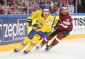 COLOGNE, GERMANY - MAY 11: Sweden's Philip Holm #5 and  Latvia's Vitalijs Pavlovs #79 skate during preliminary round action at the 2017 IIHF Ice Hockey World Championship. (Photo by Andre Ringuette/HHOF-IIHF Images)