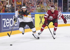 COLOGNE, GERMANY - MAY 16: Germany's Felix Schutz #55 and Latvia's Arturs Kulda #32 chase down a loose puck during preliminary round action at the 2017 IIHF Ice Hockey World Championship. (Photo by Andre Ringuette/HHOF-IIHF Images)
